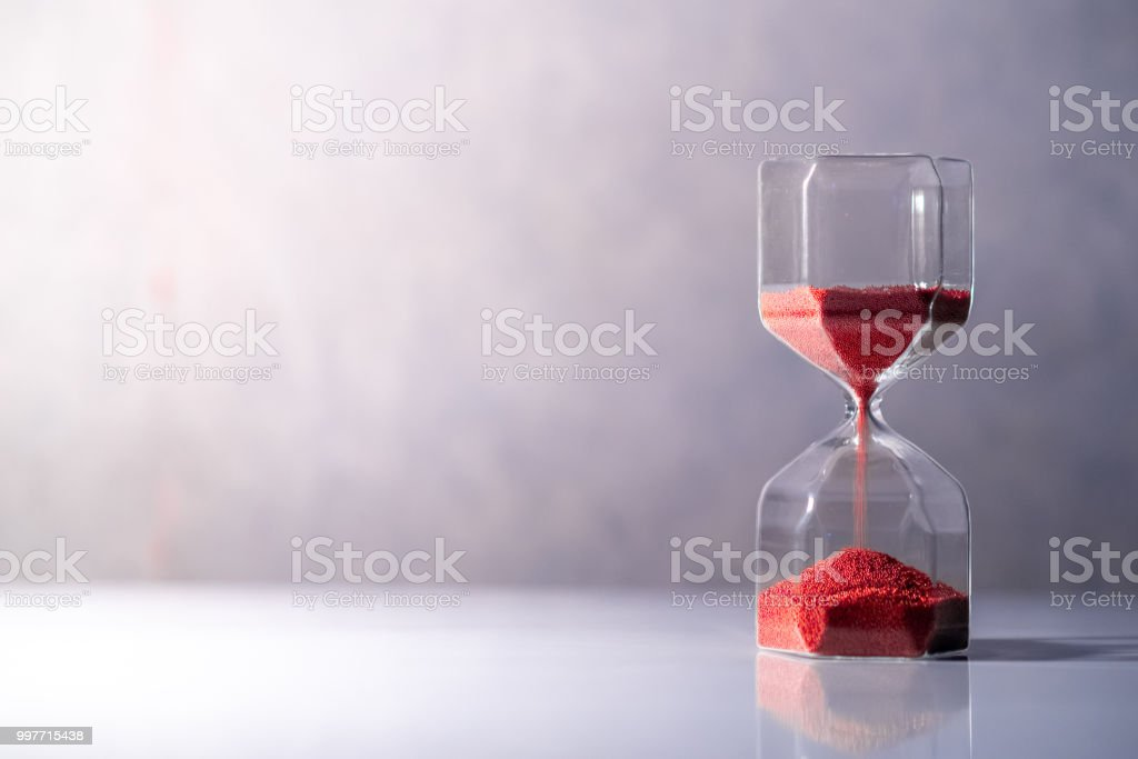 Red sand running through the shape of modern hourglass on white table.Time passing and running out of time. Urgency countdown timer for business deadline concept with copy space royalty-free stock photo