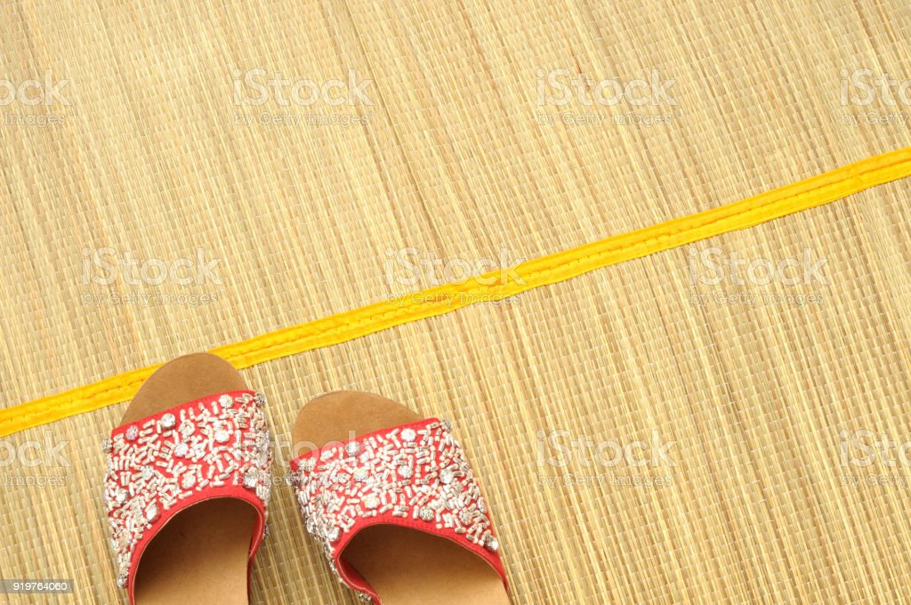 Red  sandals on a bamboo mat stock photo
