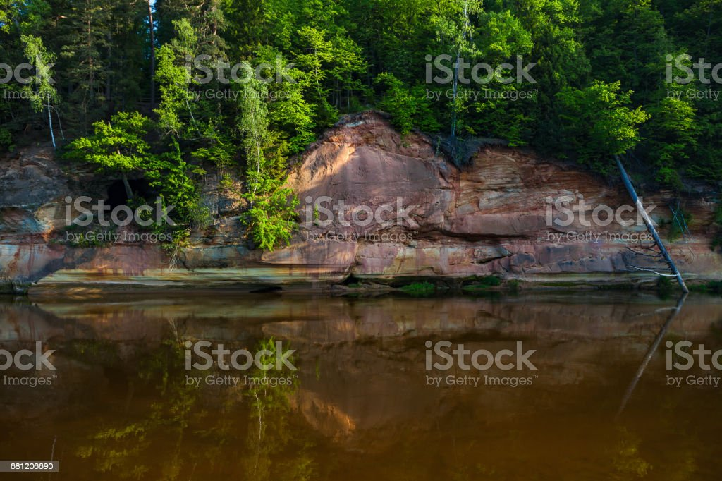 Red sandstone cliffs by the river in Gauja national park in Latvia royalty-free stock photo