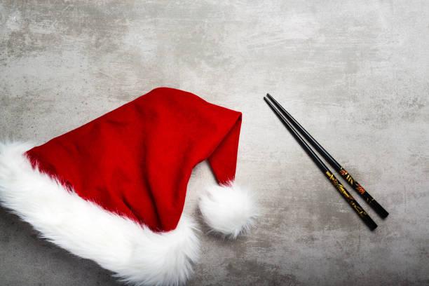 rote weihnachtsmütze und stäbchen auf einem grauen beton tisch - weihnachten japan stock-fotos und bilder