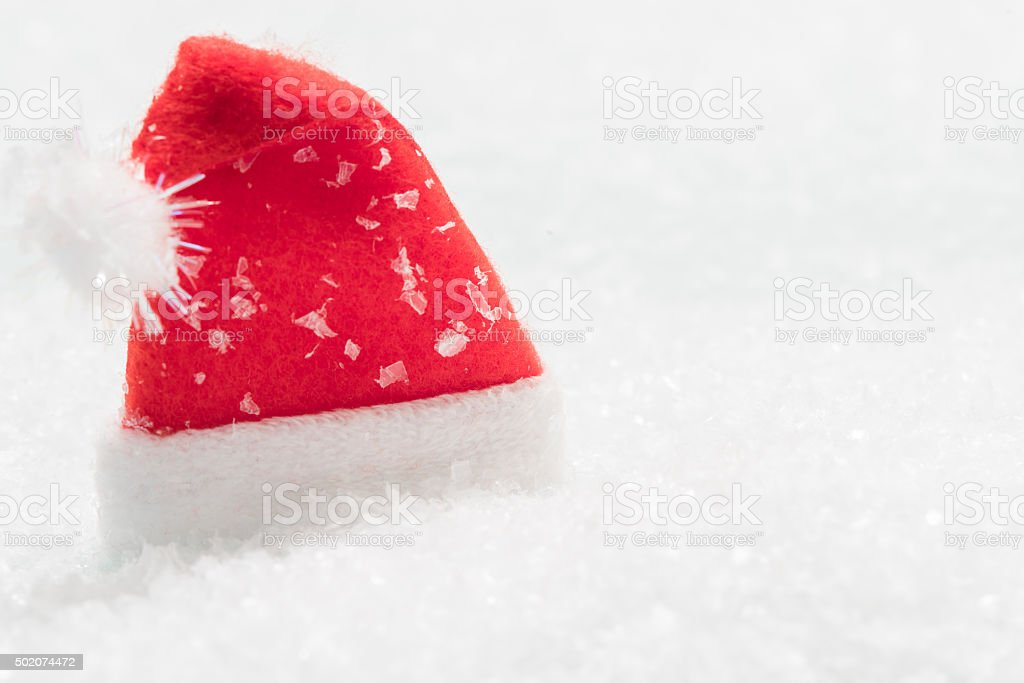 Red Santa hat in the snow stock photo