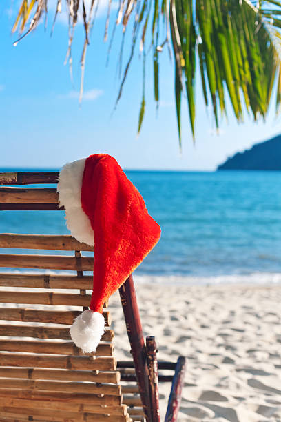 Red Santa's hat hanging on beach chair under palm tree stock photo