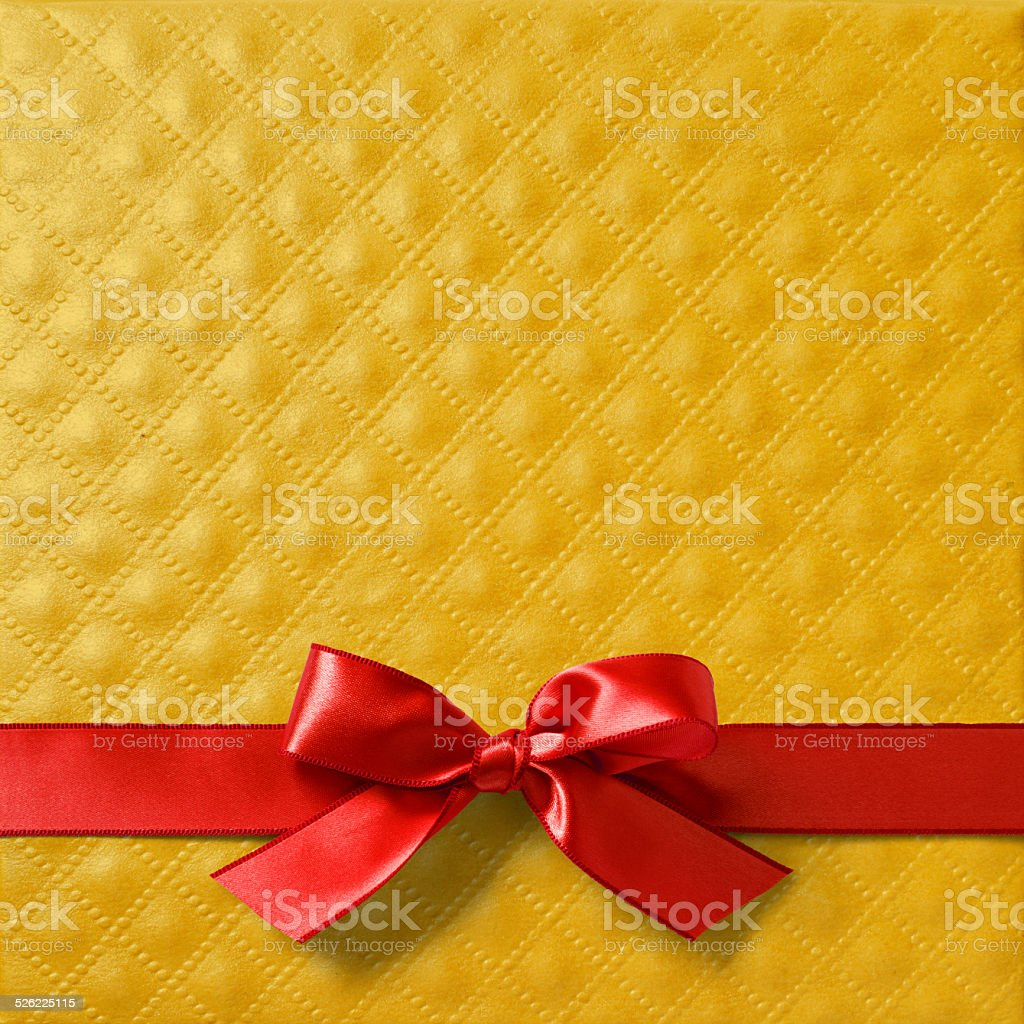 Red satin ribbon on gold paper stock photo