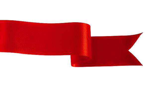 Red satin ribbon weaving through a white background stock photo