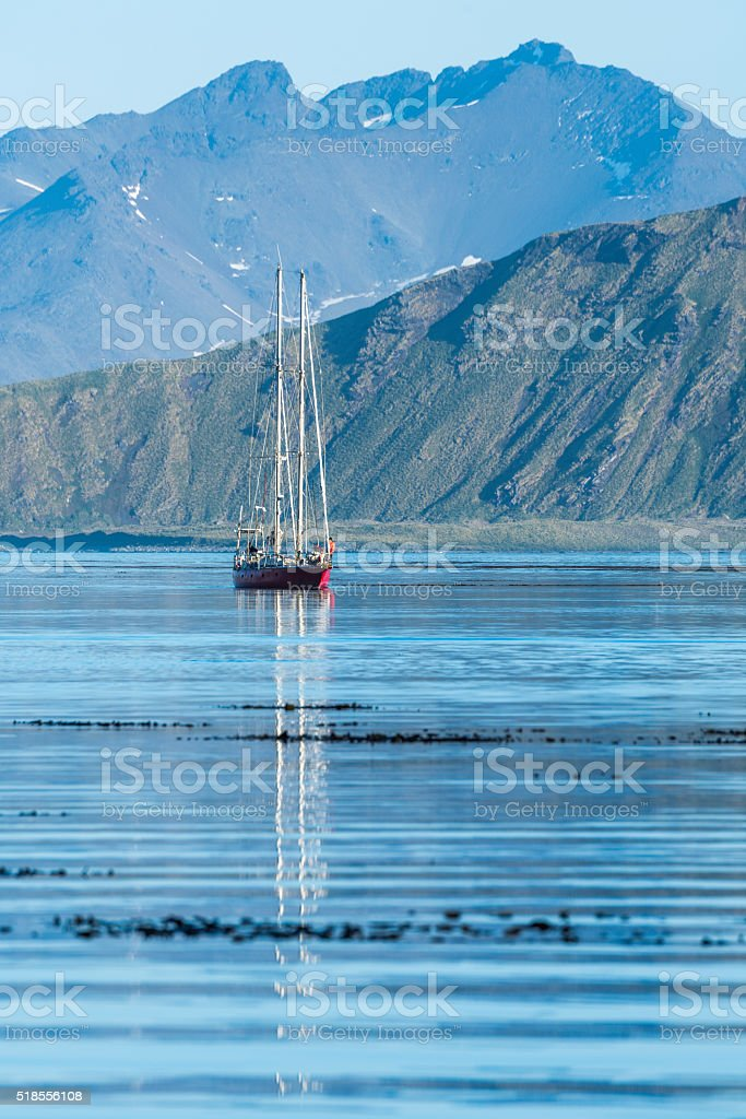 Red schooner motoring into bay past mountains stock photo