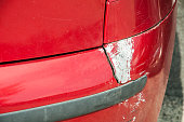 istock Red scratched car with damaged paint in crash accident or parking lot and dented damage of bumper metal body from collision 1035013276