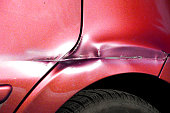 istock Red scratched car with damaged paint in crash accident or parking lot 907945880