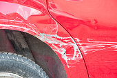 istock Red scratched car with damaged paint in crash accident or parking lot and dented metal body from collision 962822514