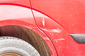 istock Red scratched car with damaged paint in crash accident or parking lot and dented metal body from collision 970360746