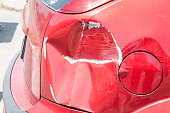 istock Red scratched car with damaged paint in crash accident or parking lot and dented damage of metal body from collision 977526180