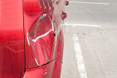 istock Red scratched car with damaged paint in crash accident or parking lot and dented damage of metal body from collision 978398618