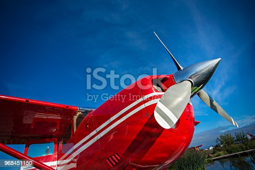 red seaplane at anchorage , alaska lake side with blue sunny sky