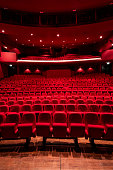 Cinema theater with Red Seats.\nRed and empty theater seats in a row