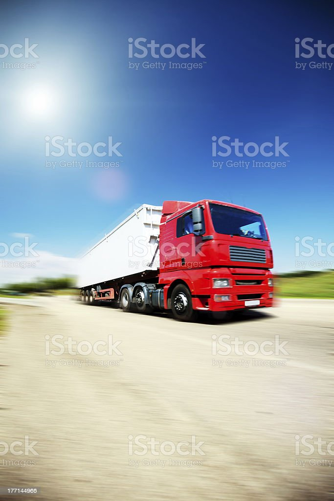 Red semi and trailer going down the road royalty-free stock photo