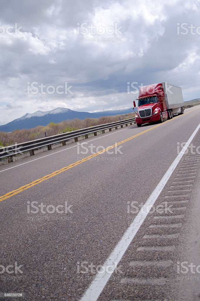 Red semi truck driving on protected highway in Nevada stock photo