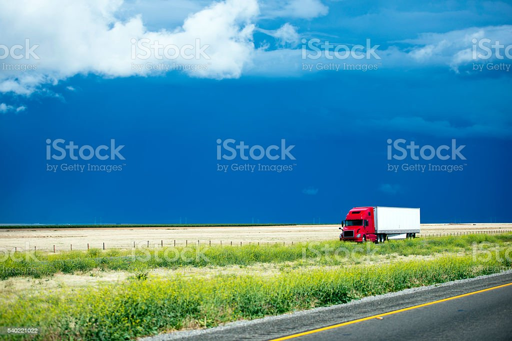 Red semi truck going with cargo on California landscaping road stock photo