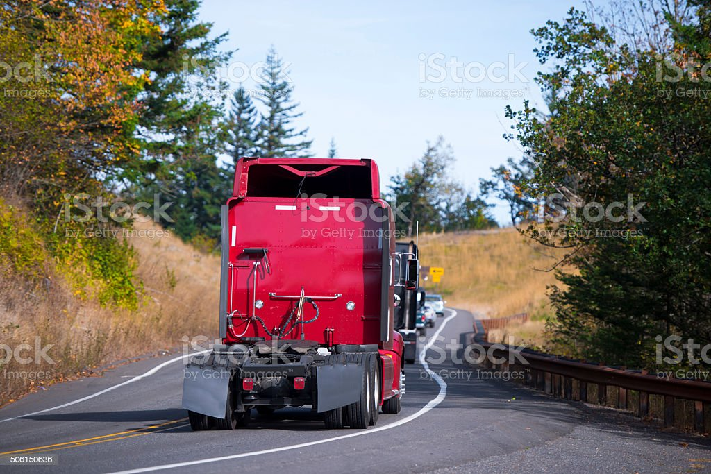 Red Semi trucks back convoy on winding fall road stock photo