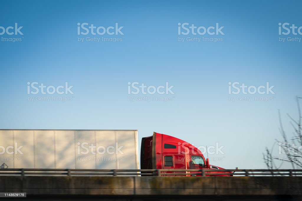 Red semi-truck 18 wheeler on highway overpass profile Tractor trailer trucking big rig on highway overpass with blue sky and copy space Blue Stock Photo