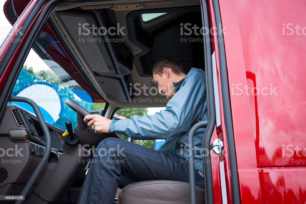 Red Semi-truck truck driver checking dashboard electronic stock photo