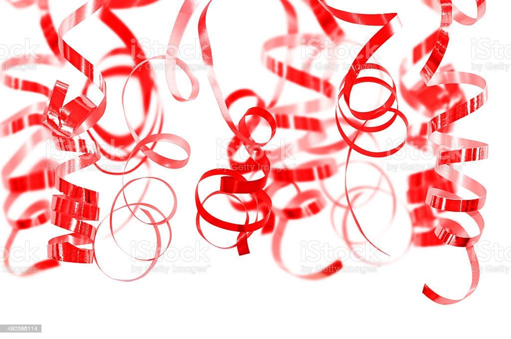 Red serpentine streamers hanging on white background stock photo