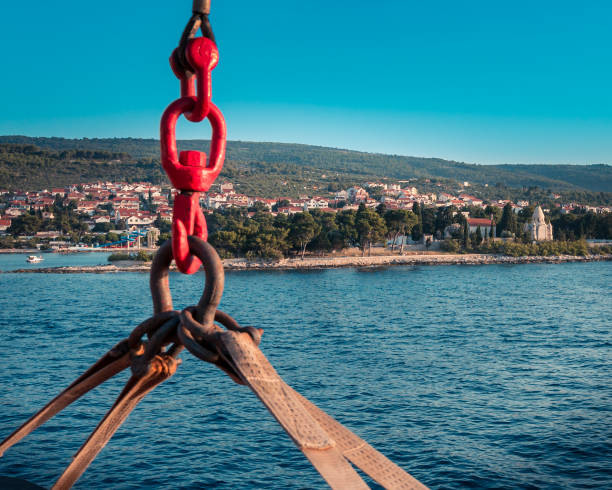 red ship hook of a passenger ferry and coastal view of Rogač on a ferry between the city of Split and the island of Šolta, Dalmatia, Rogač is the ferry port from the island of Solta hooikoorts stock pictures, royalty-free photos & images