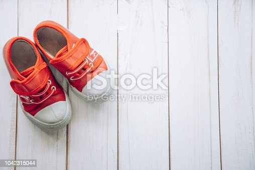istock Red shoes for children on wooden floor 1042315044
