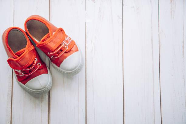 rode schoenen voor kinderen op houten vloer - shoe stockfoto's en -beelden