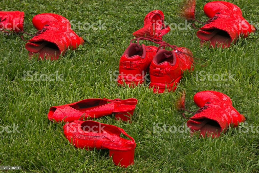 Red shoes in the meadow: the symbol of the violence against women stock photo