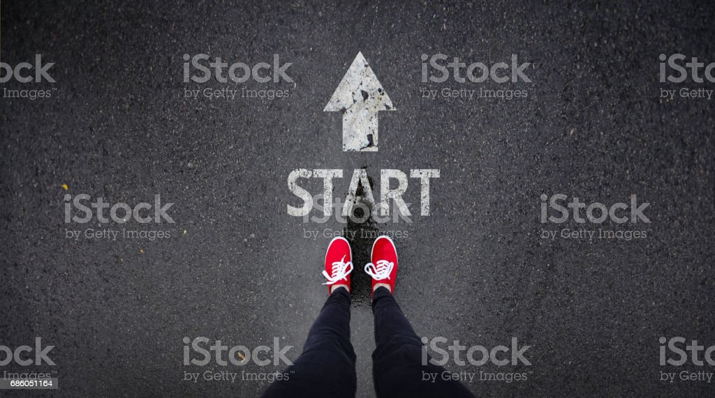 Red shoes standing next start with arrow painted on ground - Foto stock royalty-free di Abbigliamento casual
