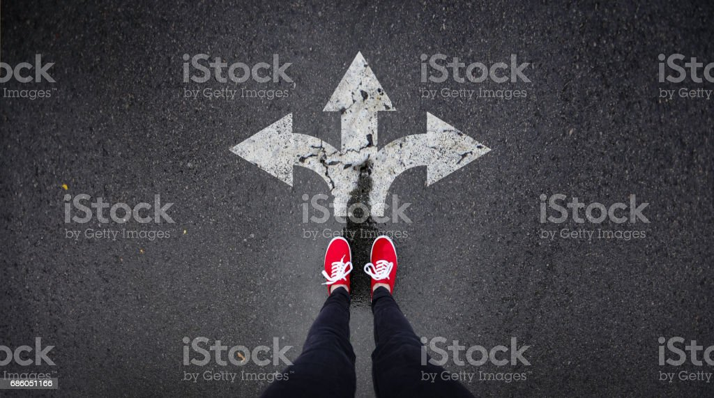 Red shoes standing next to arrows painted in road stock photo
