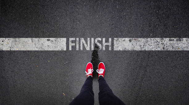 red shoes standing next to finish line painted text - finishing stock photos and pictures