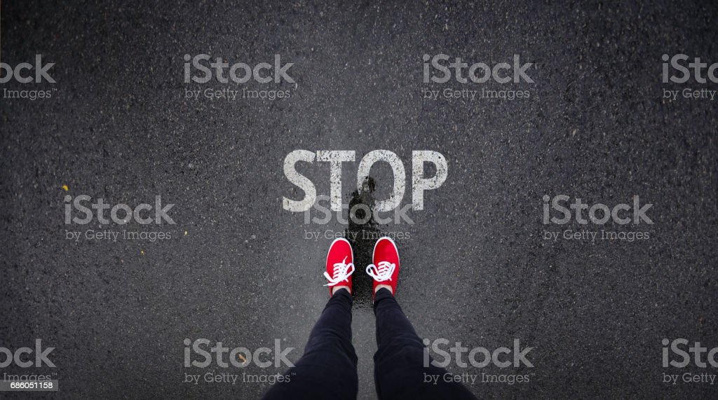 Red shoes standing next to stop sign painted on ground stock photo