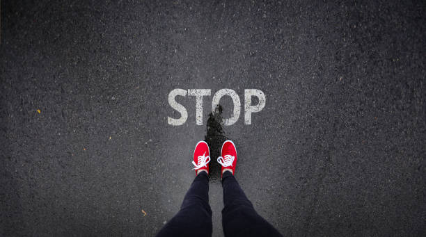 Red shoes standing next to stop sign painted on ground
