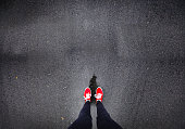 istock Red shoes walking in rain 686051192