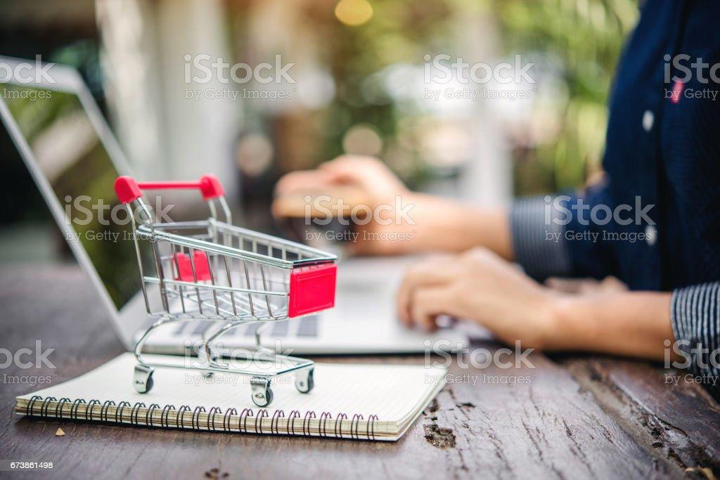 Kırmızı alışveriş sepeti ve online kavramı alışveriş ahşap masa üstünde laptop. royalty-free stock photo