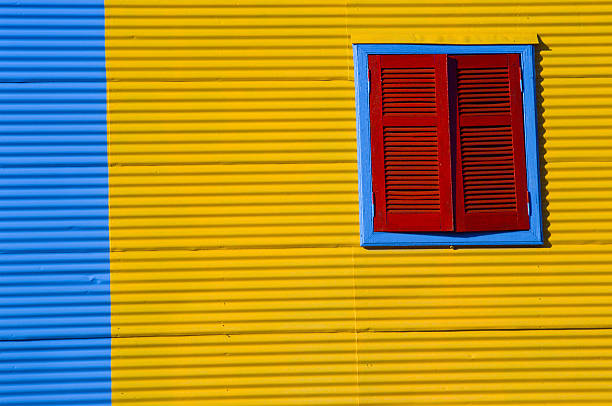 Red Shutters on a Yellow & Blue Wall stock photo