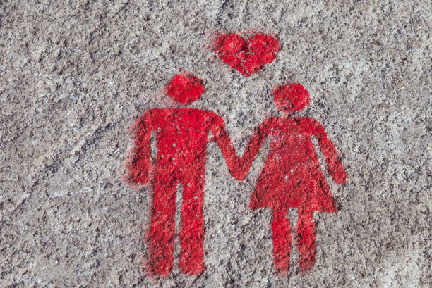 a red sign is drawn on the sidewalk of porto: the heart, man and woman hold hands. a sign of free space for couples. - people stencils silhouette stock photos and pictures