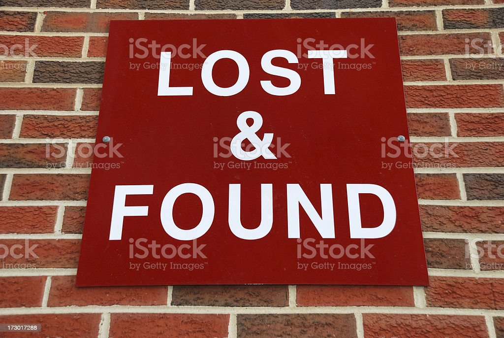 Red lost and found sign on brick wall