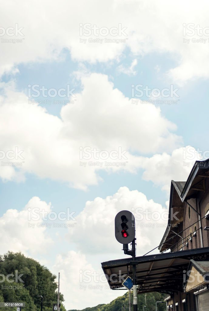 Red signal light at train station with blue cloudy sky. stock photo