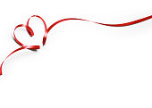 Bright red ribbon that's thin and curved into the shape of a heart. The ribbon curves around to create the heart and is not tied. One end of the ribbon curves up and then back down, and the other curves to form the shape of a point where they overlap at the bottom. Great use for love and romance concepts. Isolated on white. Clipping path is included.