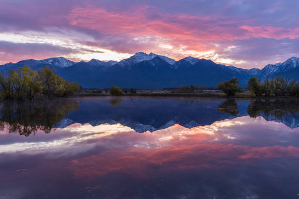Red skies reflect in the calm pond near St. Ignatius, Montana. stock photo