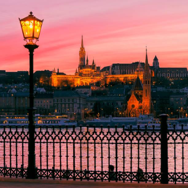 ブダペストの夕暮れのマティアス教会の上の赤い空 - マーチャーシュ教会 ストックフォトと画像