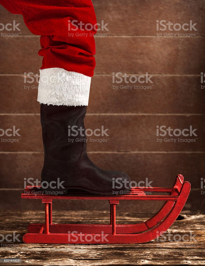 Red sled with the boot of Santa Claus stock photo
