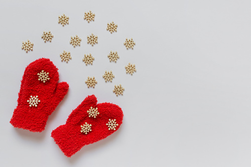 Little red kids mittens with many small wooden decorative white snowflakes and copy blank space on white background.