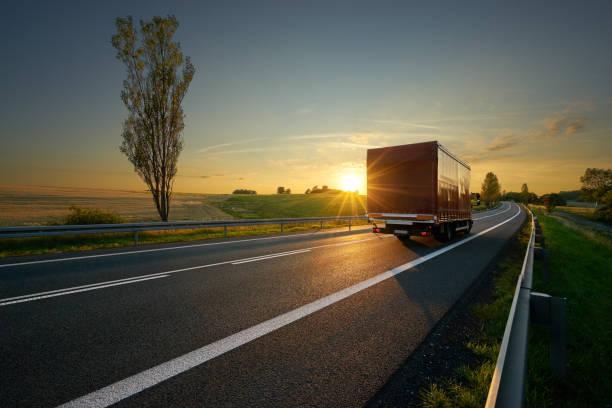 rote kleine lkw-fahren auf asphaltierten straße auf ackerflächen in ländlichen landschaft bei sonnenuntergang - pickup trucks stock-fotos und bilder