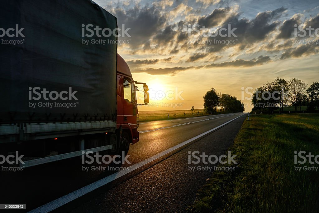 Red small truck driving on the asphalt road at sunset. stock photo