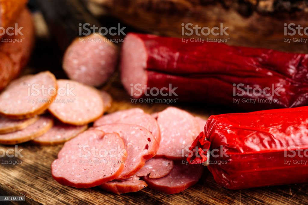Red smoked sausage on cutting board royalty-free stock photo