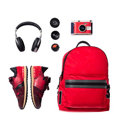 Red sneakers, backpack with camera and headphones isolated on white background (with clipping path)