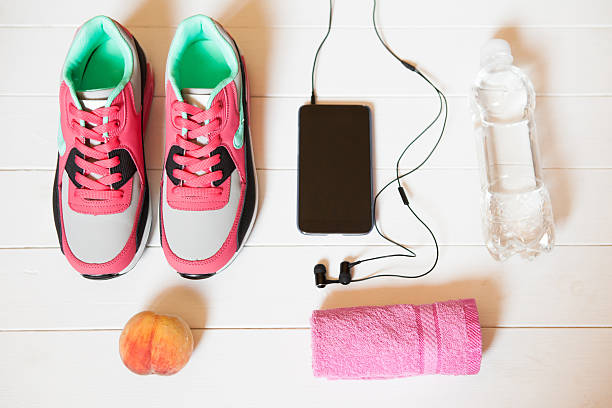 Red sneakers Red sneakers with towel, peach, bottle with water, smartphone with headphones on white wooden background indoors. Sports and fitness background, healthy lifestyle concept. knolling concept stock pictures, royalty-free photos & images