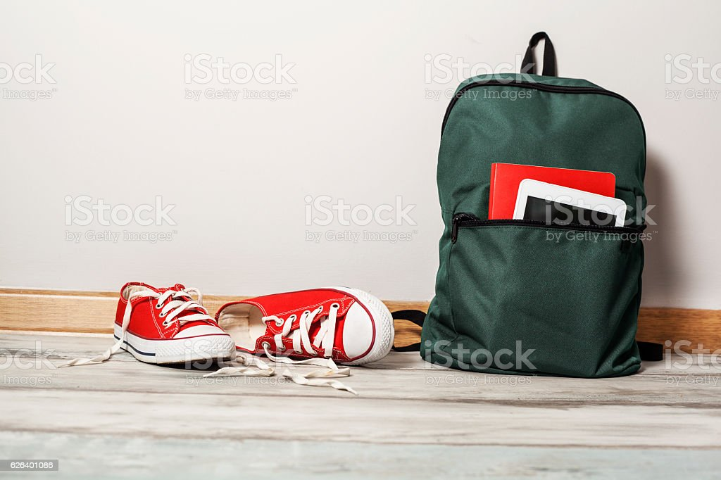 Red sneakers with school bag on wooden background стоковое фото
